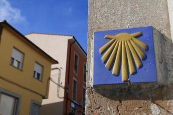 """Die Strahlen repräsentieren die verschiedenen Jakobswege und das """"Schanier"""" stellt das Ziel - Santiago de Compostela - dar. Dass ist aber nur in Asturien so. In allen anderen Teilen Spaniens weisen die Arme/Strahlen den Weg."""