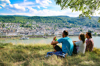 Pause auf einer Wiese an der Hangkante mit Blick auf den Rhein und Boppard.