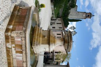 Wie gemalen: Der Dorfplatz von Greccio mit Brunnen und Kirche